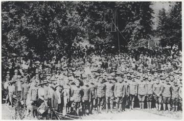 A large crowd of men in their uniforms are pictured beside the park among their peers. Subjects unidentified.
