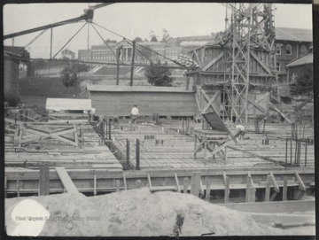 An unidentified man stands in the middle of the construction site looking around at the progress. In the background is Stalnakar Hall.