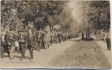 A. S. O. students march alongside the wagon of newlyweds. Subjects unidentified.