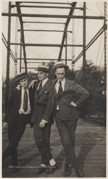 Three unidentified men put their arms around each others shoulders while posing on the bridge.