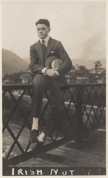 "The photograph is titled, ""Irish Nut."" An unidentified man sits on the railing while holding his hat."