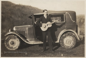 The unidentified family member stands in front of a muddy automobile while strumming the instrument.