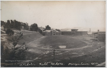 View of the field which is now where the MountainLair is located. In the background is the Armory and to the right of that is Mechanical Hall, which burned down in 1956. To the right is Commencement Hall, with grandstand attached to the back. To the left and up the hill is Stalnakar Hall.