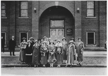 A group of women pose in front of the church entrance. Subjects unidentified.