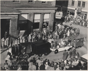 A crowd watches at the intersection of 2nd Avenue and Ballengee Street as a parade float disguised as a train drives by.