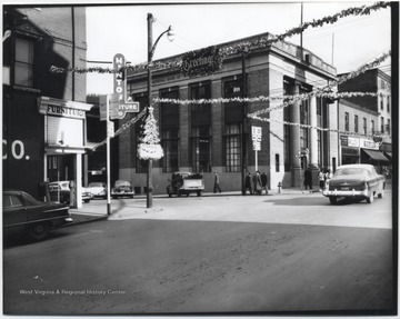 "Looking at the corner of Temple Street and 2nd Avenue, streamers zig-zag across the streets. A sign reading, ""Greetings"" hovers above the road."