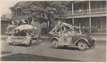 The two decorated vehicles make their way down Temple Street. The float in back advertises Plumley-Hulme Co.