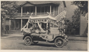 Three unidentified children sit inside the vehicle decorated with streamers and American flags on Temple Street.