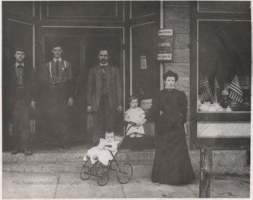 A woman and her children stand outside of the building beside three men. The building is located on Third Avenue. A sign on the entrance-way advertises Fels-Naptha soap. Subjects unidentified.