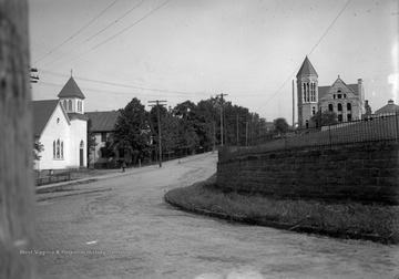 Grounds of I.C. White property (where White Hall now stands) and WVU Library which was then in the Old Administration Building (now Stewart Hall).  On the Opposite side of the street is the old Lutheran Church which was torn down. A Lutheran student chapel now stands in its stead.