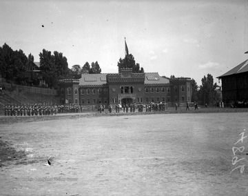 Image shows a cadet drill in front of the WVU Armory from the Agricultural Experiment Station.