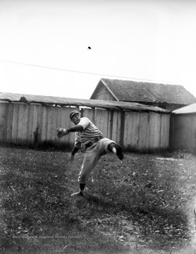 A WVU Athletics baseball player throws a ball