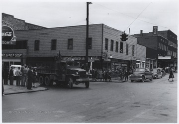 A truck carrying uniformed soldiers is pictured at the intersection of Ballengee Street and 2nd Avenue. Subjects unidentified.