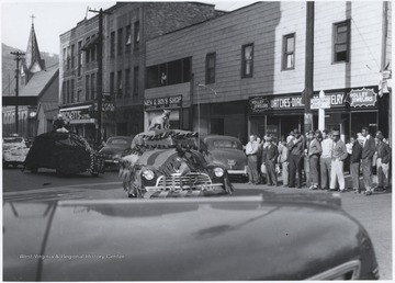A string of decorated cars make their way through the intersection of Ballengee Street and 2nd Avenue as a crowd watches from the sidelines.