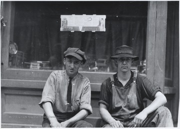 Two men, one in overalls, sit idly beside the building.