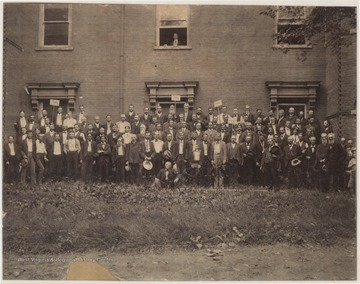 A large group of men pose beside the building with signs. Subjects unidentified.