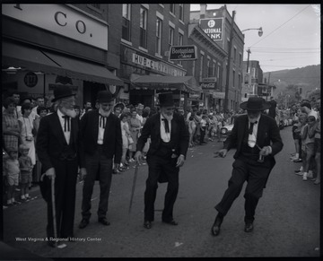 Four unidentified men wearing old-fashioned suits and full beards dance in the street while spectators watch from the sidewalks.
