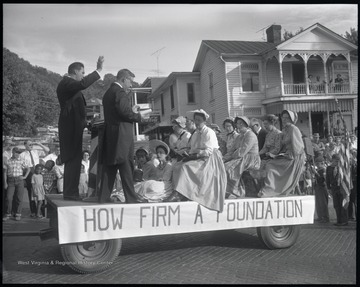 "Parade participants dressed in old-fashioned clothing sit on top of a wagon. Attached is a sign that reads, ""How Firm a Foundation."" Behind the cart, a Boy Scout troop is pictured with an American flag. Subjects unidentified."