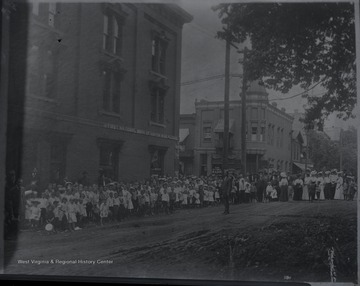 Spectators line the sidewalks beside the First National Bank of Hinton and National Bank of Summers awaiting the parade procession.  Subjects unidentified.