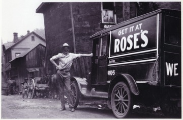 "An unidentified man stands beside the old automobile that reads, ""Get it at Rose's."""