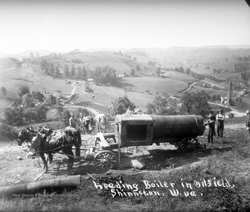 Men load a boiler towed by horses in an oil field.