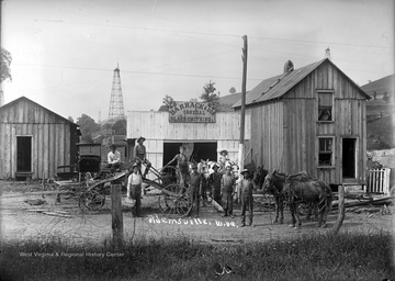 Group of unidentified men, a child, four horses, and a dog pose for a group portrait in front of Barrack & Son General Black-Smithing Store near Shinnston, W. Va.