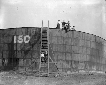 Unidentified men and women pose for portrait while standing on an oil storage tank in Morgantown, W. Va.