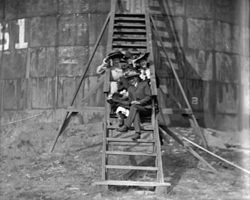 """Girls posed on ladder of oil tank"""