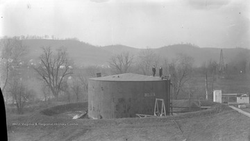 Men stand on top of an oil tank in Morgantown, W. Va.