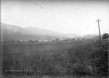 View of a farmer's field and roofs of Franklin, W. Va. in the distance