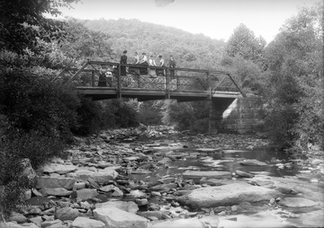 """Iron Bridge Up M & K Railroad.""  Men and women stand on a bridge over a creek."