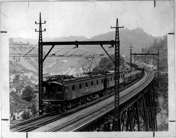 Norfolk and Western Train crossing a trestle bridge. A small community is below.