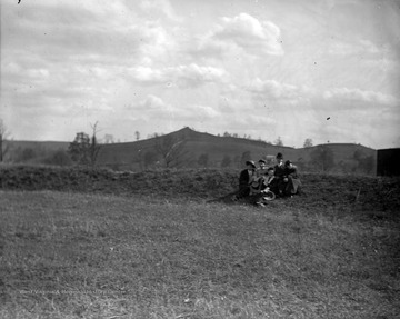 A group of unidentified subjects are pictured on a hill with Dorsey's Knob in the background.
