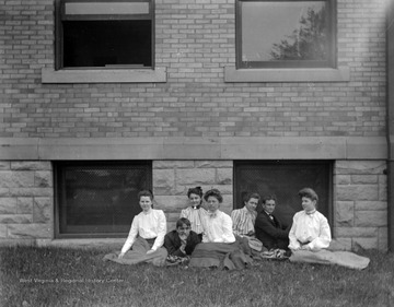 Two male and five female students of West Virginia University sit in the grass next to what is likely the Central Public School in Morgantown, W. Va.  The Central Public School was built in 1898-1899 and was opened in September 1899 to grade and high school students.