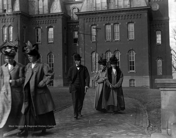 Early twentieth century students walking away from Woodburn Hall likely between classes at West Virginia University.
