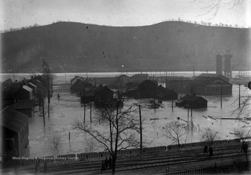 "The flooded town is shown with mountains in the background and the ""P.R.R. Railroad tracks in foreground."""