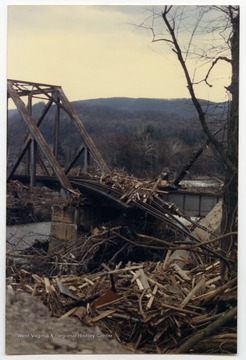 Debris surrounds the damaged bridge and railroad tracks.  The damage occurred during the November 1985 flood in the area around Parsons, Elkins, Onego, and Mounth of Seneca, W. Va.