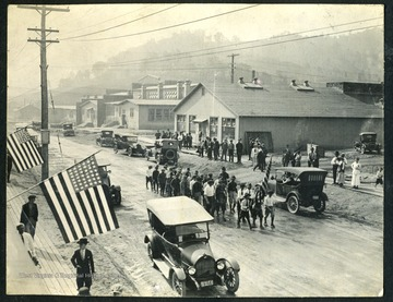 Unidentified boys and men march in a parade down the street in Nitro, with factories in the background. Nitro was created during WWI in 1917 to produce gunpowder for the war effort.