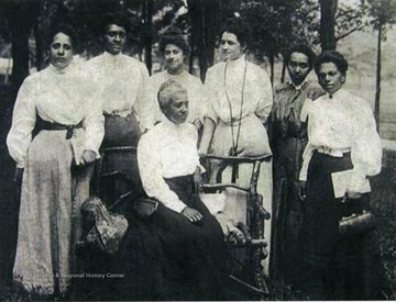 Women of the Niagara Movement at Storer College in Harpers Ferry, W. Va.  Left to right are Mrs. O. M. Waller, Mrs. H. F. M. Murray, Mrs. Mollie Lewis Kelan, Mrs. IdaD. Bailey, Miss Sadie Shorter, and Mrs. Charlotte Hershaw.  Mrs. Gertrude Wright Morgan is seated.
