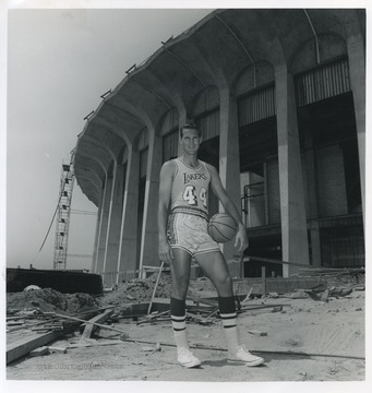 West is pictured holding a basketball on the construction site of the L.A. Forum.  He played for the Lakers from 1960-1974.