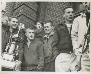 Jerry West, pictured holding the trophy, is outside of East Bank High School after leading his team to championship victory. West was the team's starting small forward. He was named All-State from 1953–56, then All-American in 1956 when he was West Virginia Player of the Year, becoming the state's first high-school player to score more than 900 points in a season.