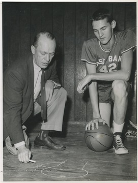 West, right, is pictured with East Bank coach Roy Williams, who is stressing defense techniques. West was the team's starting small forward. He was named All-State from 1953–56, then All-American in 1956 when he was West Virginia Player of the Year, becoming the state's first high-school player to score more than 900 points in a season.