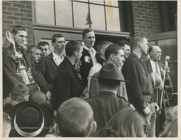 Jerry West, pictured on the left holding a trophy, is outside of East Bank High School after leading his team to championship victory. West was the team's starting small forward. He was named All-State from 1953–56, then All-American in 1956 when he was West Virginia Player of the Year, becoming the state's first high-school player to score more than 900 points in a season.