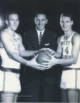 West, right, poses with West Virginia University Basketball Coach Fred Schaus, center, and teammate Willie Akers, left, while holding a basketball. West played for West Virginia University before he was drafted by the Los Angeles Lakers.