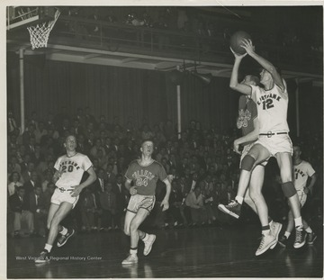 With this shot, West (No. 12) makes the shot that scores him a new state high school record of 860 points in a season with only 6:50 left in the game. Also on the court is Bob Green (No. 20) of East Bank and Bob Short (No. 24) of Mullens.West was East Bank High School's small starting forward. He was named All-State from 1953–56, then All-American in 1956 when he was West Virginia Player of the Year, becoming the state's first high-school player to score more than 900 points in a season.In 1956, West led his team to secure its first ever state championship title.