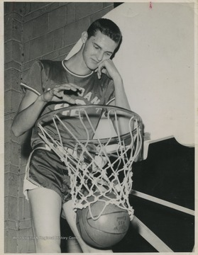 West is pictured throwing a basketball through the basket nonchalantly. He was East Bank High School's small starting forward.West was named All-State from 1953–56, then All-American in 1956 when he was West Virginia Player of the Year, becoming the state's first high-school player to score more than 900 points in a season