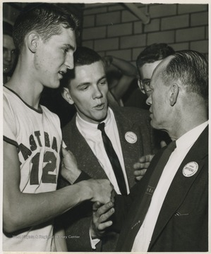 East Bank High School basketball coach Roy E. Williams, right, shakes the hand of Jerry West, left, in the dressing room after beating Mullens High School in Morgantown and winning the state championship title.West was East Bank's starting small forward. He was named All-State from 1953–56, then All-American in 1956 when he was West Virginia Player of the Year, becoming the state's first high-school player to score more than 900 points in a season.
