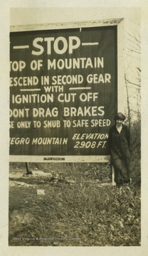 An unidentified woman poses next to a sign for Negro Mountain. Negro Mountain is a part of the Allegheny Mountains that extends from Deep Creak Lake, Maryland to  Pennsylvania. The woman pictured is likely standing next to a sign on Interstate-68 in Maryland.