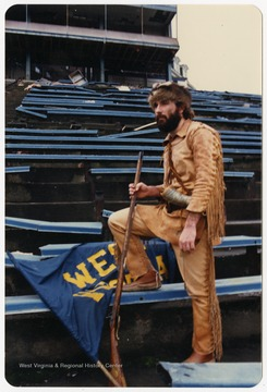 West Virginia University's 1986-1987 mascot poses on Old Mountaineer Field bleachers before demolition.