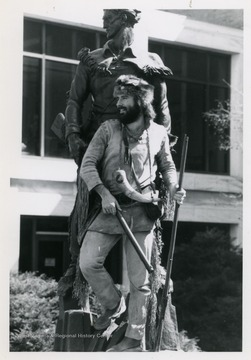West Virginia University's 1986-1987 mascot poses with Mountaineer Statue located outside of the Mountainlair on the downtown campus.